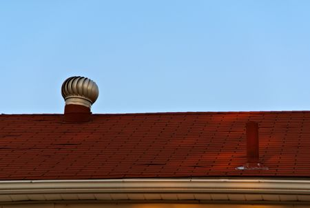 A pair of vents on the red roof of a residental building.