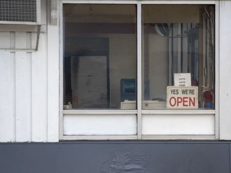 A view of a store front with sign in the window. Stock Photo