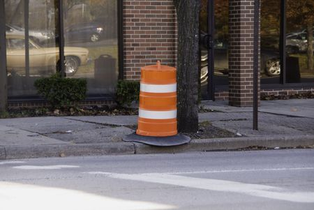 A city street with traffic reflections, wavy sidewalk, and orange barrell. Stock Photo - 7906547