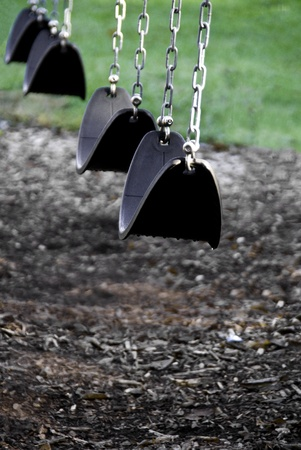 Sling type swings made of leather like or rubber material hung by chains.