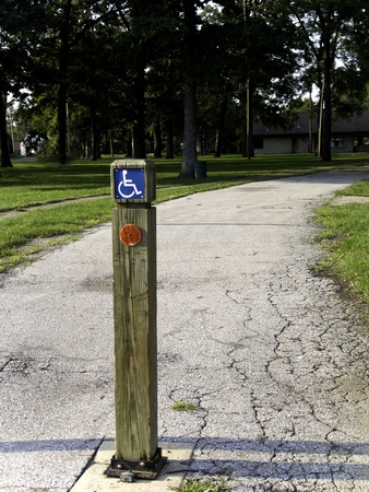 walking path: A post near a walking path into set of trees with a handicap sign just outside a metropolitan park.