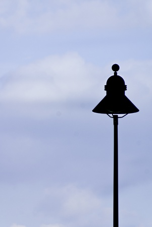 A street lamp silhouette againt a slightly overcast blue sky. Stock Photo - 10401610