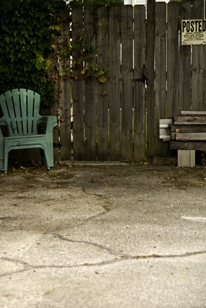 old items: A grungy privacy fence with an old chair and other left items.  Stock Photo