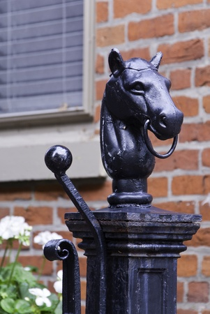 hitching post: A worn hitching post used as a garden ornament.