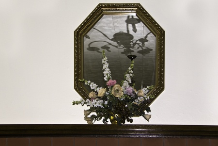 mantel: An arrangement of flowers on a mantel and  in front of a mirror with a reflection of a chandelier.