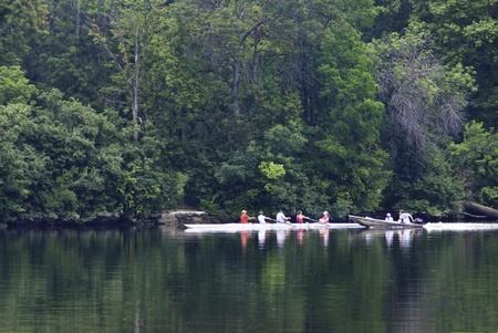 Een groep roeiers op een kalme rivier omgeven, maar groen. Stockfoto - 12547157