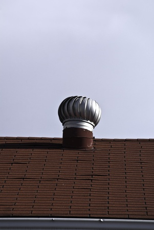 An attic vent on a red tiled rooftop.