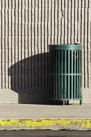 A green trash can in a public area near a brick wall on a sidewalk with a curb.