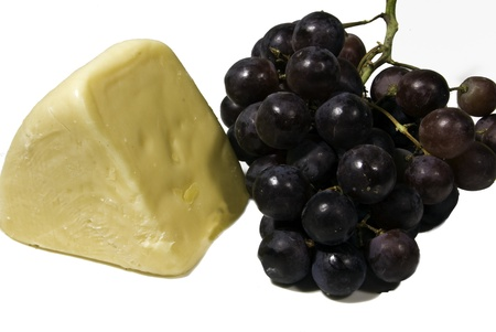 chees: A chunk of chees and a bunch of red grapes.