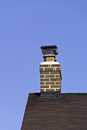 An edge of a roof with a chimney and screen.  photo