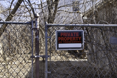 A private property sign on a fence with bramble in the background.