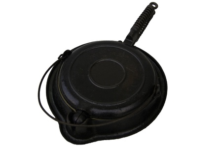 stovetop: A black and vintage stovetop waffle iron.