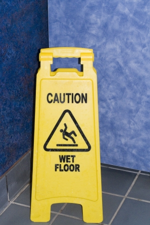 A caution stand warning of wet floors on a blue floor with blue walls.