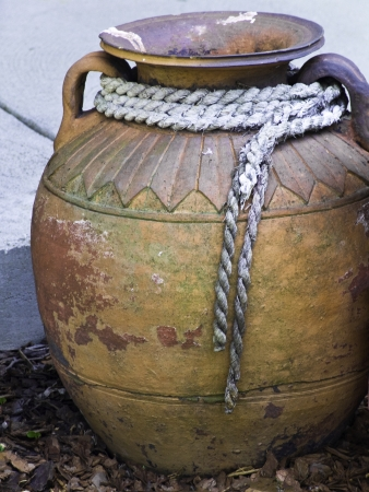 An old clay jug used for decoration on a modern patio. Banco de Imagens - 14620685