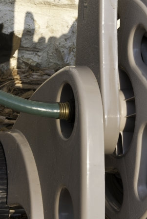 A close up view of a hose connection and reel.