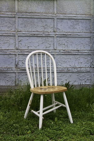 bedraggled: An old peeling door with a discarded chair in front.