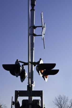 A railroad crossing signal on post with lights and signs.
