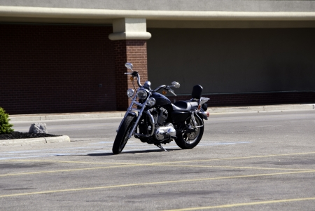 A motorcyckle sitting alone in an empty parking lot.