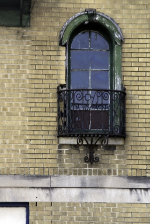 balcony window: A cream colored brick wall with an old and grunge like window and balcony.