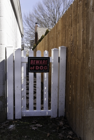 A beware of dog sign on a gate between a wall and a fence.