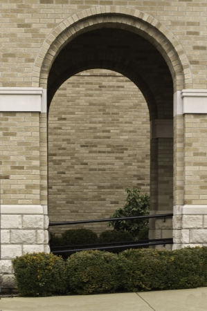 brich: An archway in a brich wall outlined with green bushes.  Stock Photo