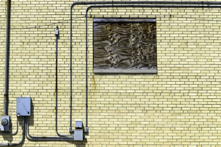 A boarded up window on a brick wall wtih boxes and pipes.  Stock Photo
