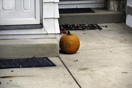 オレンジ カボチャのハロウィーン装飾ドアのステップで。