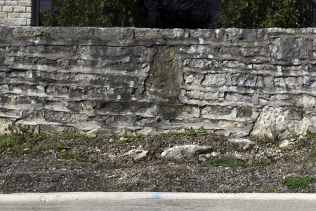 A old and rugged stone wall with uneven layers of cement.