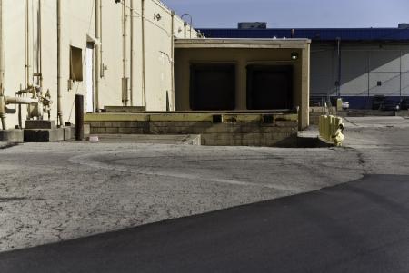 A warehouse loading dock with doors, poles, and asphalt.  Stok Fotoğraf