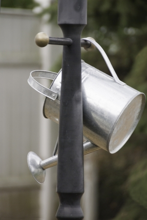 A watering can hanging from a lamppost in a garden.