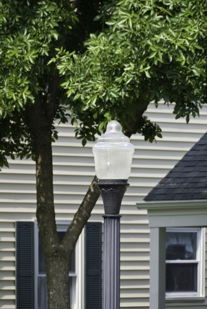 typical: A street lamp in a typical neighborhood with a house in the background.  Stock Photo