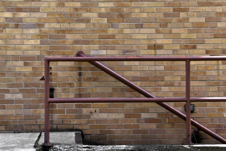 hand rail: A red hand rail along a birck wall and stairway.  Stock Photo