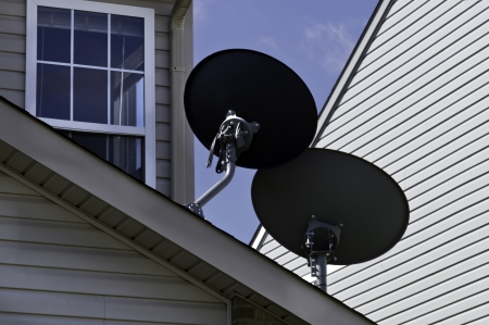 A pair of communication dishes on the roof of a house.