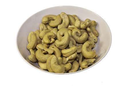 A light gray bowl of cashews on a white background.  Stock Photo