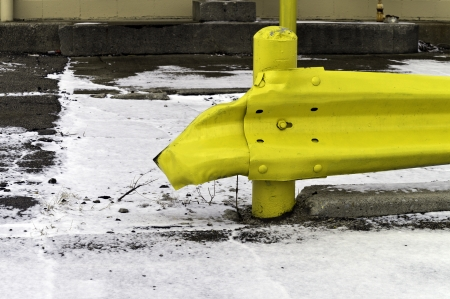 A yellow crumpled guard rail behind a warehouse and on white snow.