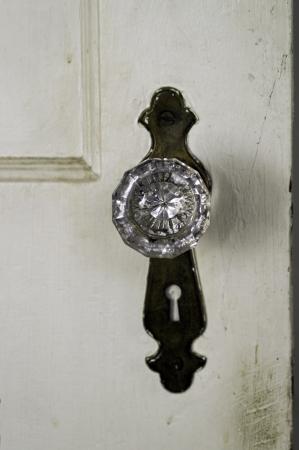 A glass door knob on an aging door.