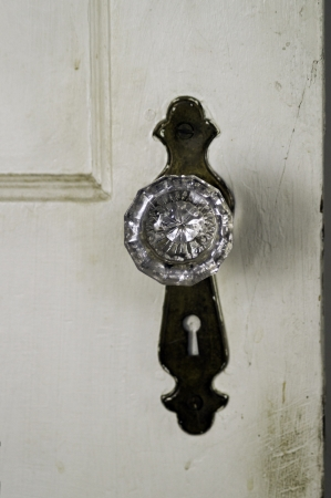 door knob: A glass door knob on an aging door.