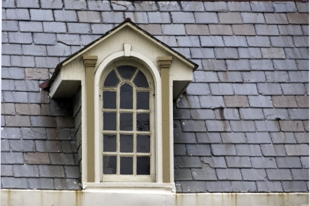 An old, ornate window surrounder by gray slate roof shingles.