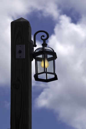 A lamp post and lit light blub against a blue sky with clouds.