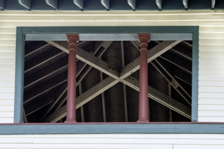 rafters: Rafters and poles seen through an open window of a building.  Stock Photo