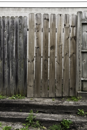A wooden fence with a wooden gate and wooden steps.  Stock fotó