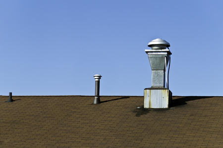 vents: A roof top with several vents also bright blue sky.