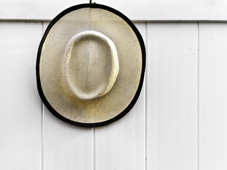 A straw hat trimed in black handing on a white wall.