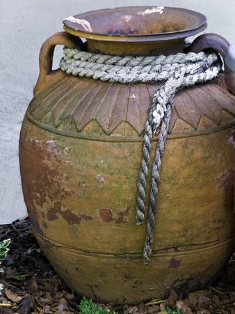 An aging ornate clay jug with a fraying rope at the neck.  Reklamní fotografie