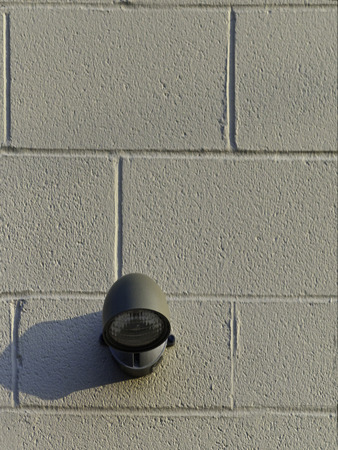 light fixture: A cement block wall with a single outside light fixture.