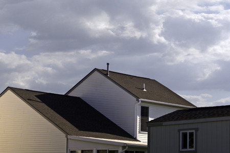 cladding tile: A view of house tops and  cloud filled sky.
