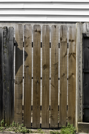 An aging wooden fence below a wall of white siding.