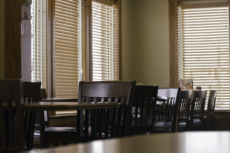 Chairs and tables and blines and windows and sunlight.  Stock Photo