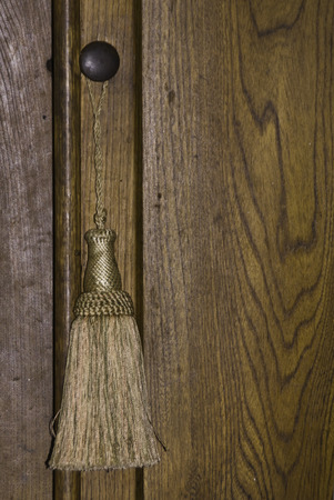 A wood door and know with a golden tassel hanging.