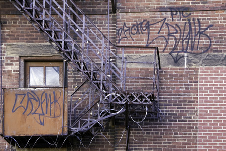 A fire escape on an on red brick warehouse wall.